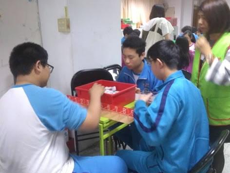 學生幫忙將社會大眾捐贈的發票以月份分裝,以便核對發票。