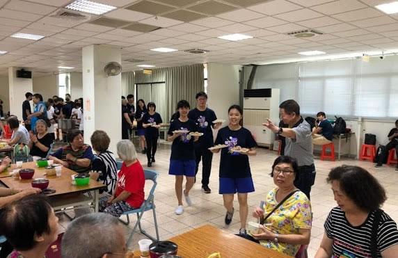 每位參與服務的學生面帶微笑端菜給長者用餐。