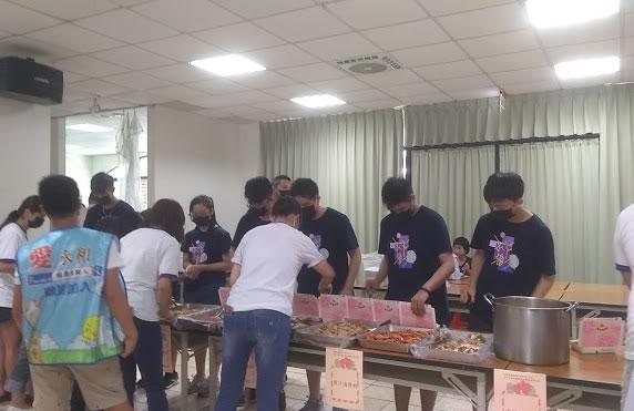 學生將現場菜餚平均分配到每份餐食中。